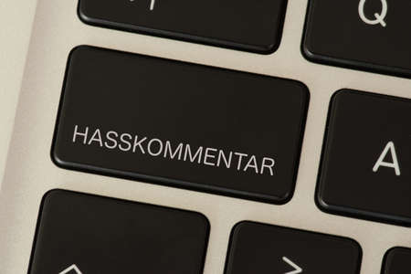 A computer and a button with the hate comment print Stock fotó