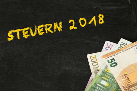 Chalk board, euro bills and taxes for the year 2018