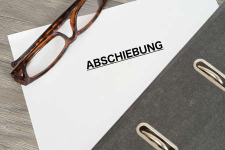 A folder, reading glasses and a document with the heading Deportation