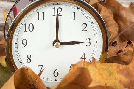 Liście i zegar zmiany czasu na czas zimowy