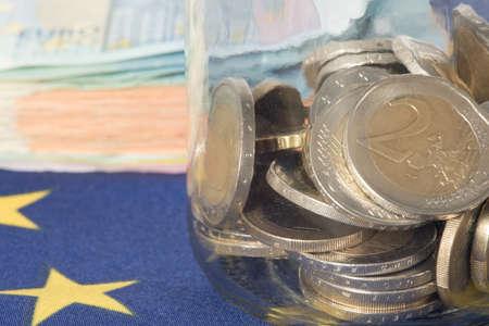 Flag of the European Union EU, euro bills and coins in a mason jar