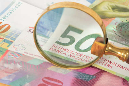 Swiss franc bills and a magnifying glass Imagens