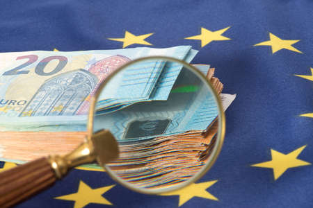 Flag of the European Union EU, a magnifying glass and euro bills