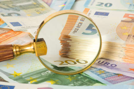 A magnifying glass and many euro bills