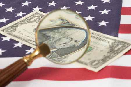 A magnifying glass, flag of USA and dollar bills