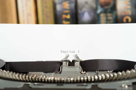 Typewriter, books and the beginning of the book Writing
