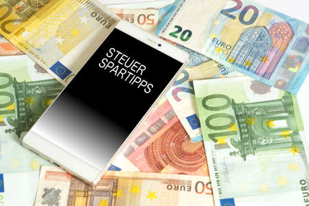 Euro banknotes and a smartphone with the tax savings tips Stock Photo