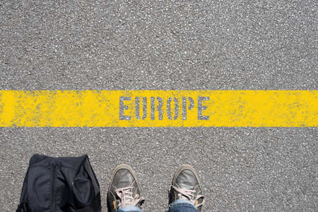 A man with a suitcase is standing on the border of the Europe