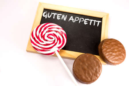 Two biscuits, a lollipop and a chalkboard with the text Bon appetit