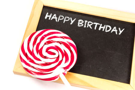 A lollipop and a chalkboard with the text Happy Birthday