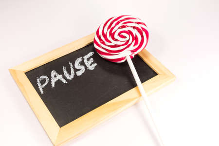 A lollipop and a chalkboard with the text Pause