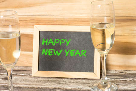 Champagne or sparkling wine and New Year wishes on a chalkboard