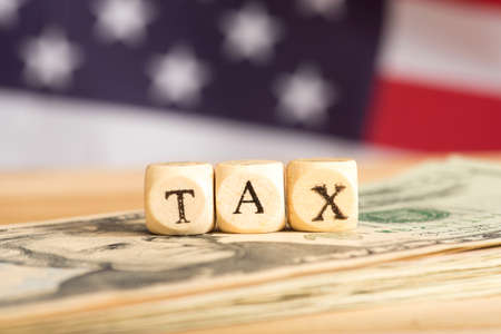 Dollar bills, American flag and the word taxes Stock Photo
