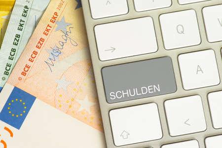A computer keyboard with a debt key Banco de Imagens