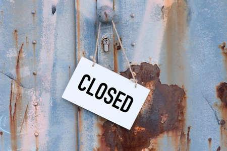 Een oude, roestige deur met een gesloten teken