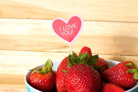Fresh strawberries and a sticker with the slogan I love you Stock Photo