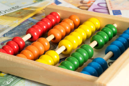 A traditional abacus and many Euro banknotes Фото со стока