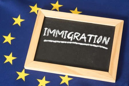 Flag of the European Union EU and a chalk board with the word immigration