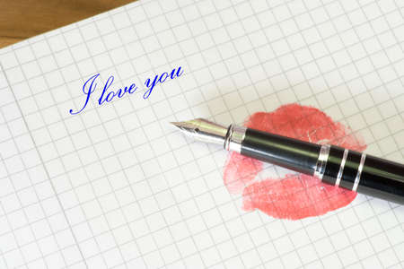 An imprint of red lips on a letter and a text I love you
