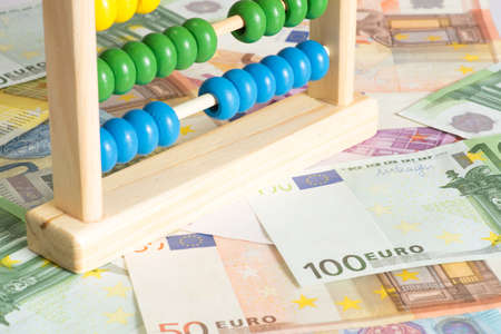 A traditional abacus and many Euro banknotes