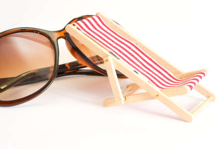 Sunglasses and a deck chair on a vacation