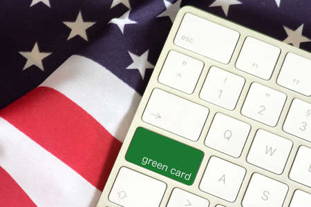 American flag, computer keyboard and the key with the imprint Green Card