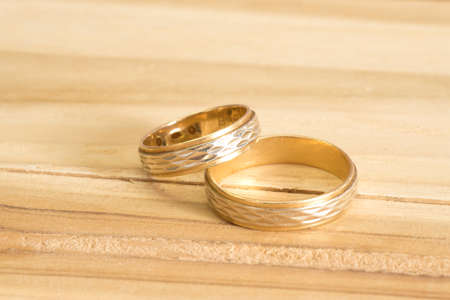 Two golden wedding rings on a wooden table