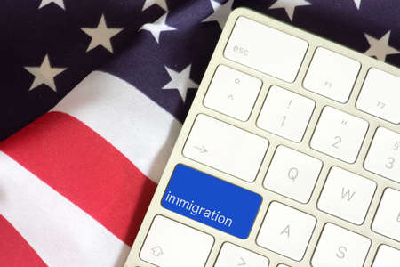 American flag and a computer with the button Immigration Banco de Imagens