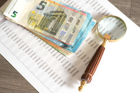 A magnifying glass, cash and a spreadsheet Stock Photo