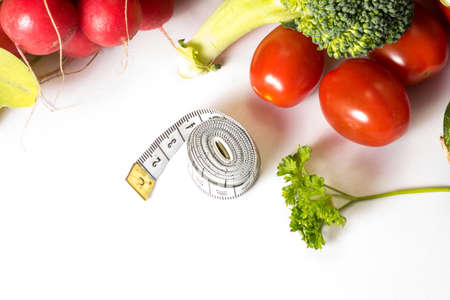 A measuring tape at a diet and various vegetables