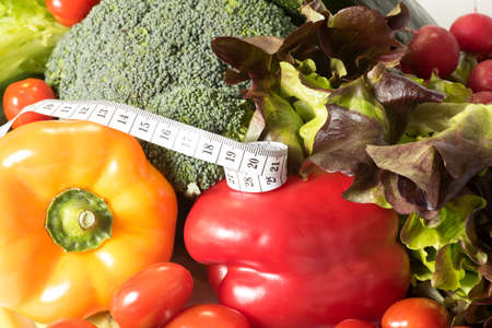 A measuring tape and various vegetables for a diet