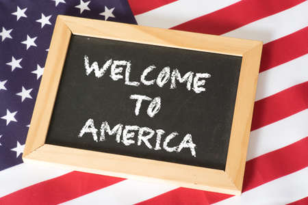 American flag and a chalk board with the word Welcome to America