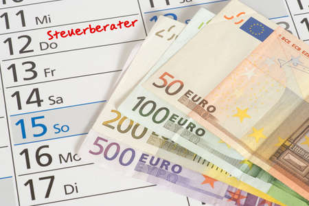 A calendar with the appointment at the tax consultant and euro banknotes Stock Photo