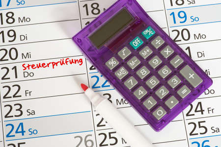 A calendar with the date for a tax audit and a calculator Stock Photo - 102105852