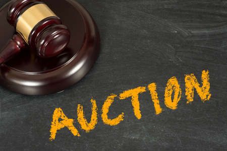 An auction hammer and chalk board with the word auction