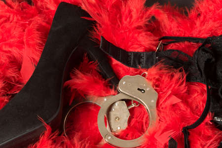 High heels, handcuffs and lingerie on a red feather pattern