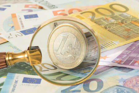 A magnifying glass, euro bills and euro coins Imagens