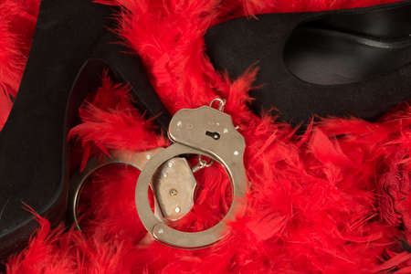 High heels and handcuffs on a base of red feathers Stock Photo