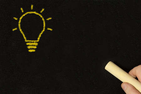 A man at the blackboard draws a lightbulb as a symbol of an idea Stock Photo