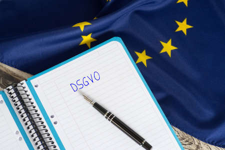 A fountain pen, exercise book, flag of the EU and data protection basic regulation DSGVO