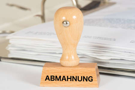 A folder and a stamp with the words Abmahnung