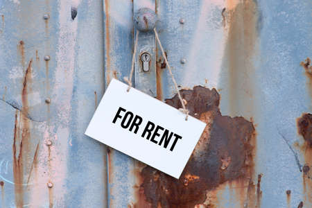 An old, rusty door and a sign for rent Stock Photo