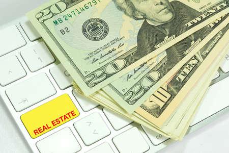 A computer, dollar bills and real estate