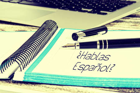 A computer, fountain pen and exercise book with the text Do you speak Spanish
