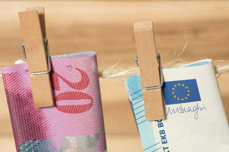 Swiss franc and euro banknote on a clothesline with clothespin Stock Photo