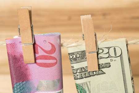 Swiss franc and dollar bills on a clothesline and clothespin