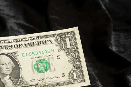 One dollar bill on black background