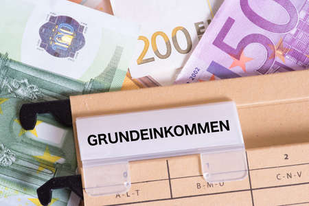Euro banknotes and a hanging folder with the imprint Basic Income in German