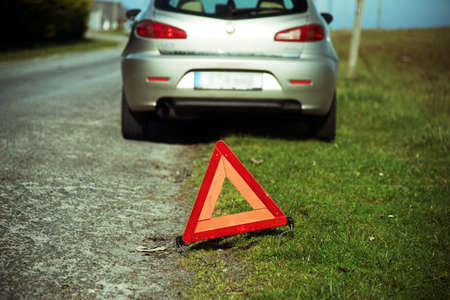 A broken-down car and a warning triangle