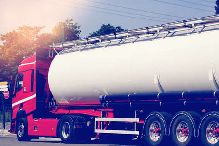 A truck with a tanker drives at sunset Stock Photo